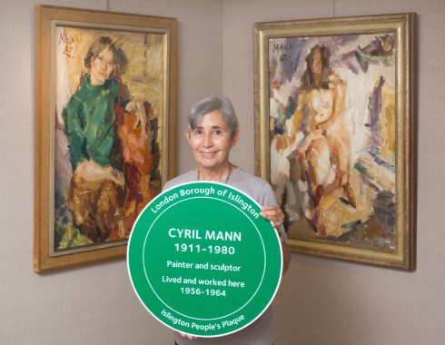 Renske with plaque in front of two pictures of her done by Cyril Mann.