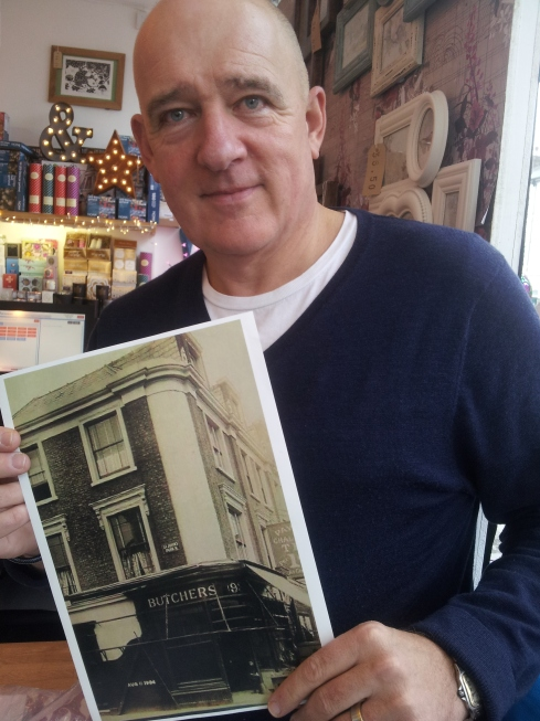 Ian Morris with a 1904 photo of his shop. Back then it was a butcher's shop. Even now the pink-fronted Map Gift Shop on Junction Road has butchers' hooks.