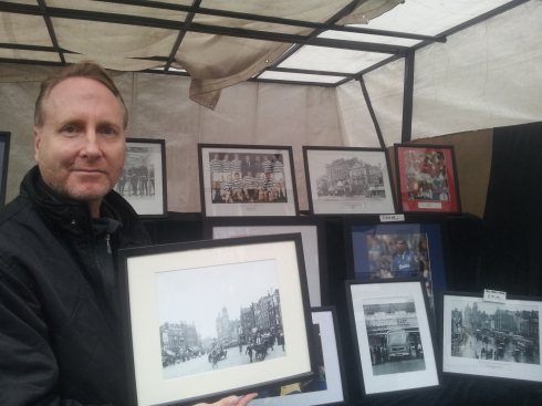 Chapel Street stall holder Christopher Curtis, who sells old photos of Islington & football prints, holds up the 1920 view he has of Islington High Street when the Islington Empire was in its heyday.