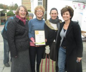 Four celebrating Plimsoll Roaders at the Blackstock Triangle Gardeners' autumn Cake Sunday holding the certificate that says the Plimsoll Road won Islington in Bloom 2015's BEST STREET. Photo, taken by Naomi Schillinger, of (L-R) Dorothy, Caroline, Judith and Nicolette.